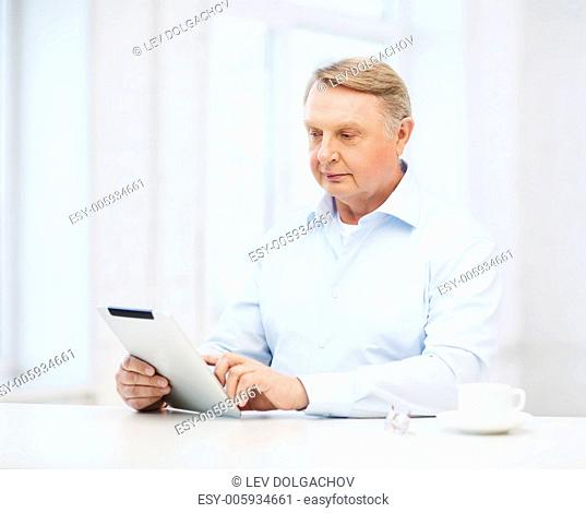 business, office, oldness, school and education concept - old man wearing eyeglasses with tablet pc computer at home
