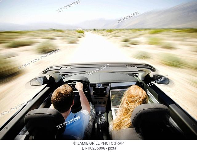 Couple driving through desert in convertible car