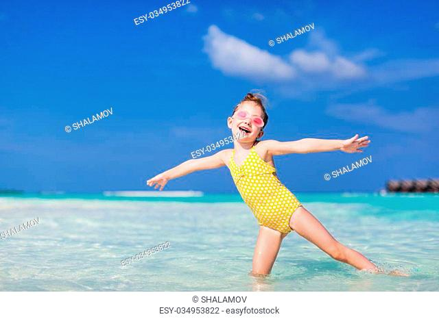 Adorable little girl splashing in tropical water during summer vacation