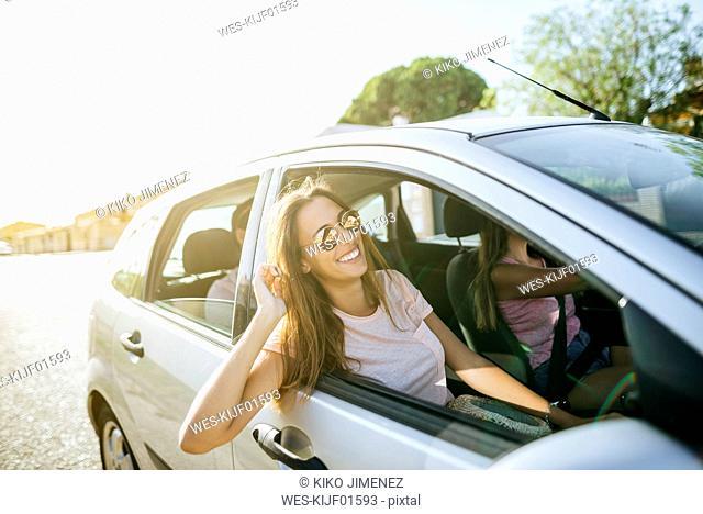 Happy friends in car seen from outside