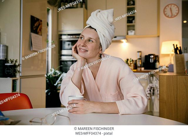 Portrait of smiling woman wearing a towel turban sitting with cup of coffee at table in the kitchen