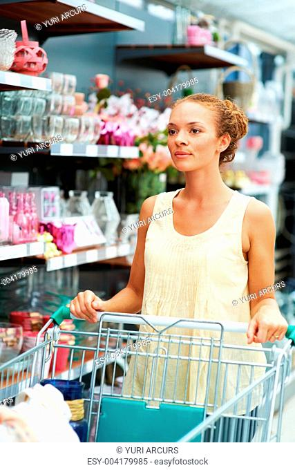 Attractive young ethnic woman looking ahead pushing trolley in aisle