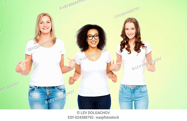 friendship, diverse, body positive and people concept - group of happy different size women in white t-shirts pointing finger to themselves over green natural...