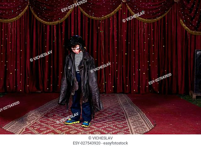 Young Boy Wearing Clown Make Up Standing on Stage in Over Sized Leather Jacket with Red Curtain in Background
