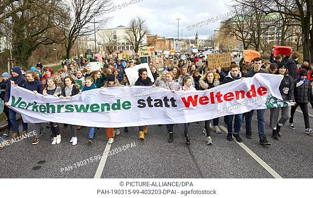 "15 March 2019, Hamburg: Climate activists hold a banner on the Lombardsbrücke with the inscription: """"Verkehrswende statt Weltende"""" during the """"Fridays for..."