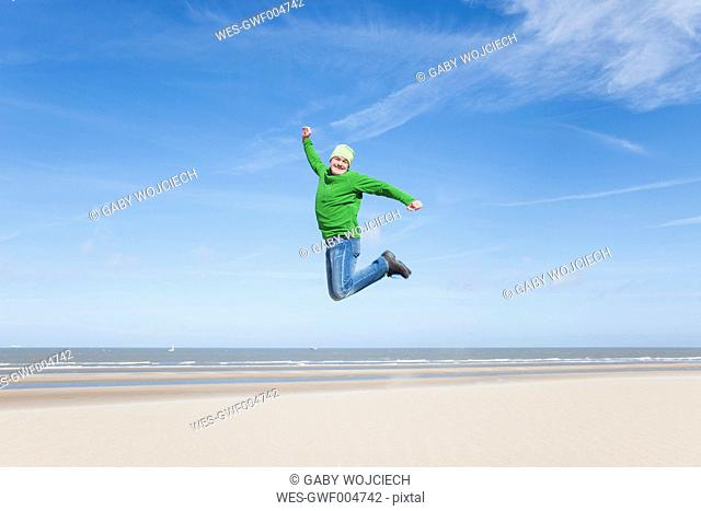 Enthusiastic mature man jumping on beach