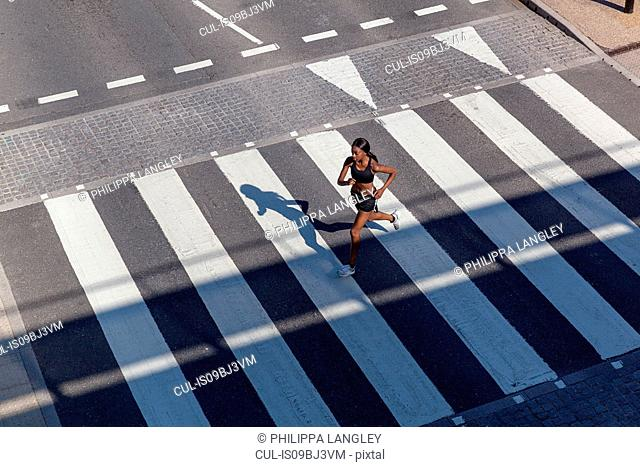 Young woman running on zebra crossing