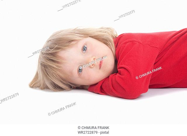 boy with long blond hair lying down, looking at camera - isolated on white