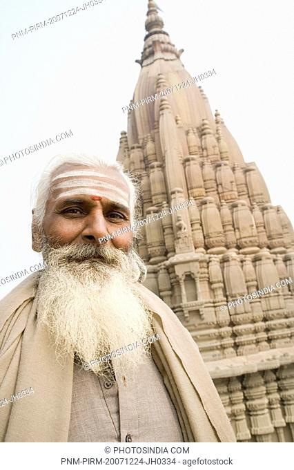 Portrait of a sadhu with a temple in the background, Scindia Ghat, Ganges River, Varanasi, Uttar Pradesh, India