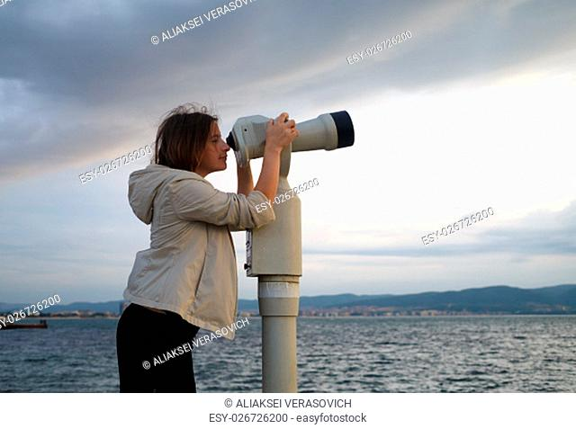 Pretty young woman using a coin operated binocular enjoying a great view of the Black sea. Early morning. Shallow depth of field. Focus on the model
