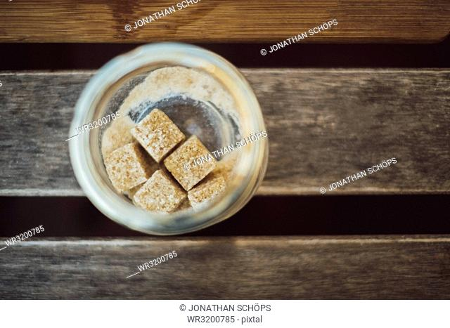 Glass with brown cubed sugar on wooden table