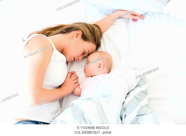 Mother and baby asleep in bed