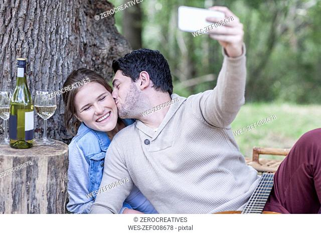 Happy young couple having a picnic with white wine taking a selfie