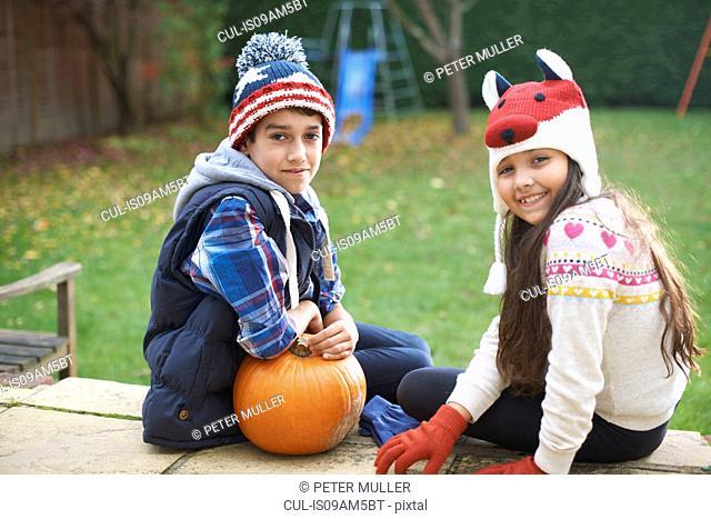 Siblings sitting on steps in garden