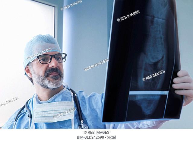 Hispanic surgeon examining x-ray