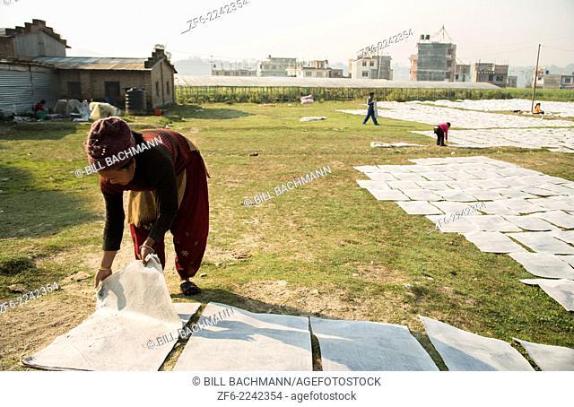 Kathmandu Nepal. working with newspaper spread on ground in Nayapati, Eastern Kathmandu. 31
