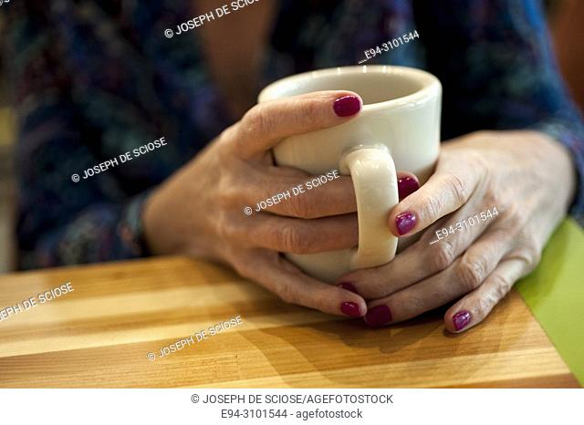 A close-up of a woman's hands wrapped around a white coffee mug in a restaurant