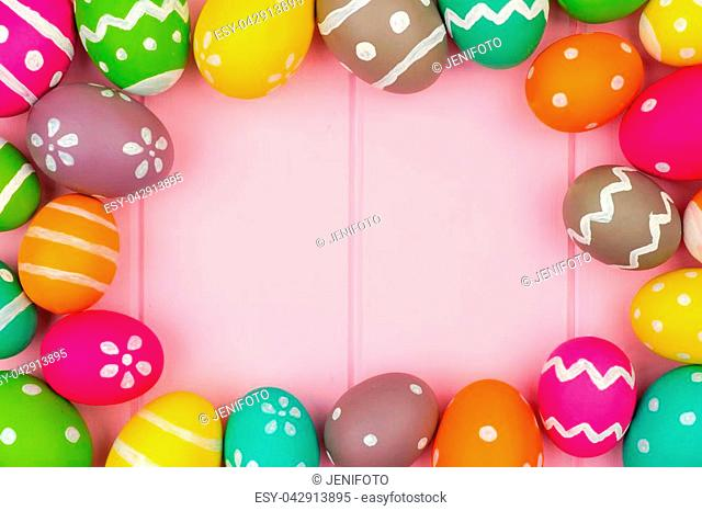 Colorful Easter egg frame against a pink wood background. Top view with copy space