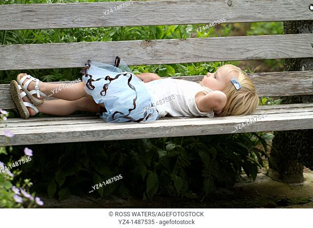 A young female Caucasian toddler on a park bench outdoors
