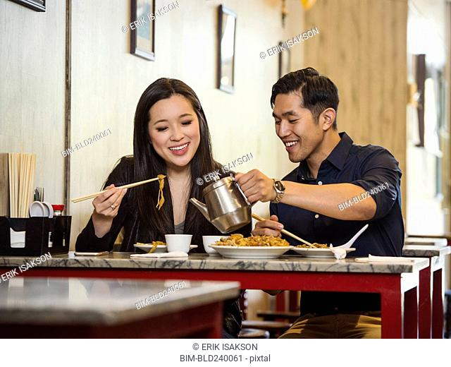 Chinese man pouring tea for woman in restaurant