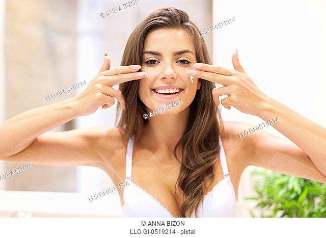 Woman has fun during applying moisturizer on the face. Debica, Poland