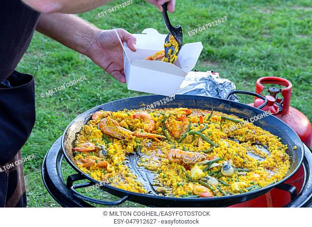 A large pan of seafood paella being served outdoors