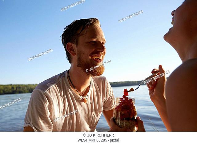 Happy couple at a lake taking a healthy snack