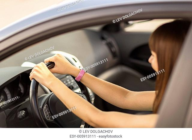 transportation and vehicle concept - happy woman driving a car