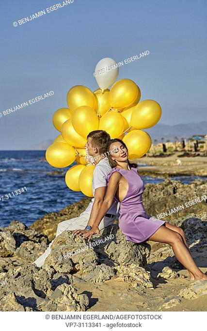 couple sitting at seaside, leaning against each other, with balloons