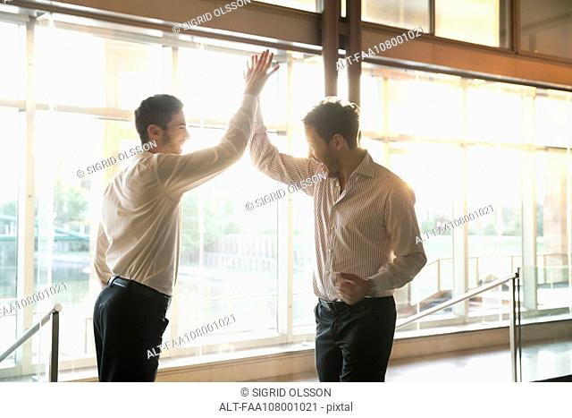 Businessmen exchanging high-five