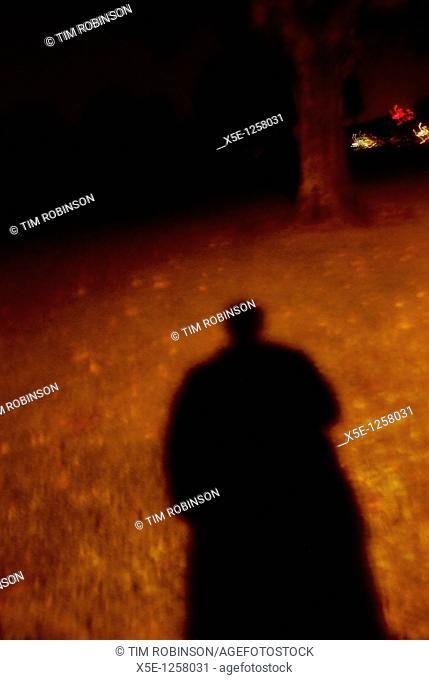 Sinister shadow of figure under streetlight