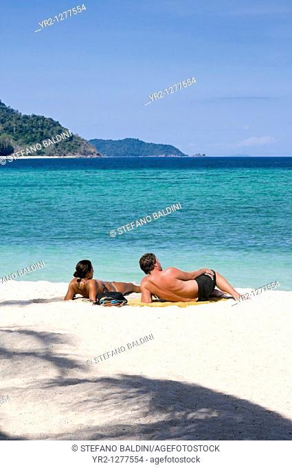 Couple sunbathing on beach,Ko Lipe,Thailand