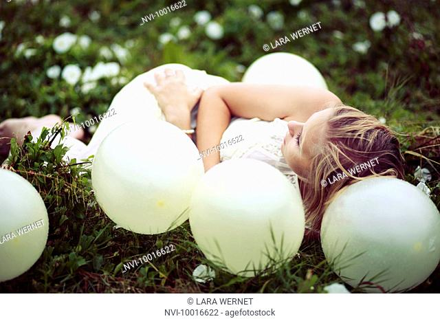 Young woman lying on a meadow between balloons