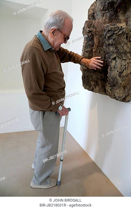 Man with visual impairment touching a sculpture at Yorkshire Sculpture Park