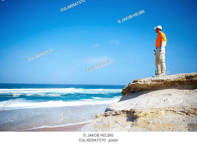 Low angle view of golfer standing on cliff overlooking ocean looking away