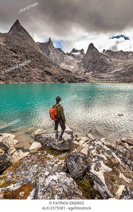 Hiker views the dramatic granite spires of the Arrigetch Peaks reflecting in a mirror calm mountain lake, Gates of the Arctic National Park, Alaska