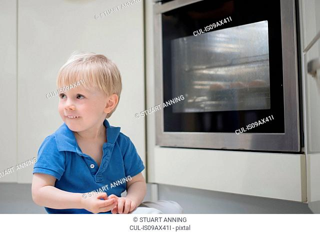 Young boy sitting on floor in kitchen, beside oven