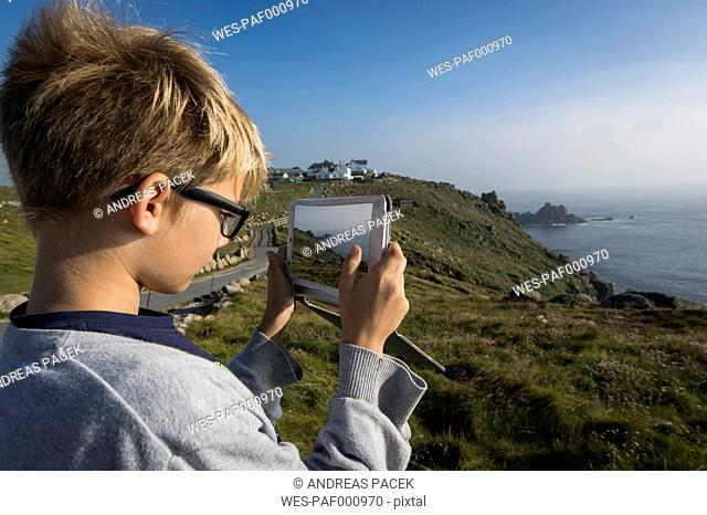 UK, Cornwall, boy photographing landscape at Land's End with his digital tablet