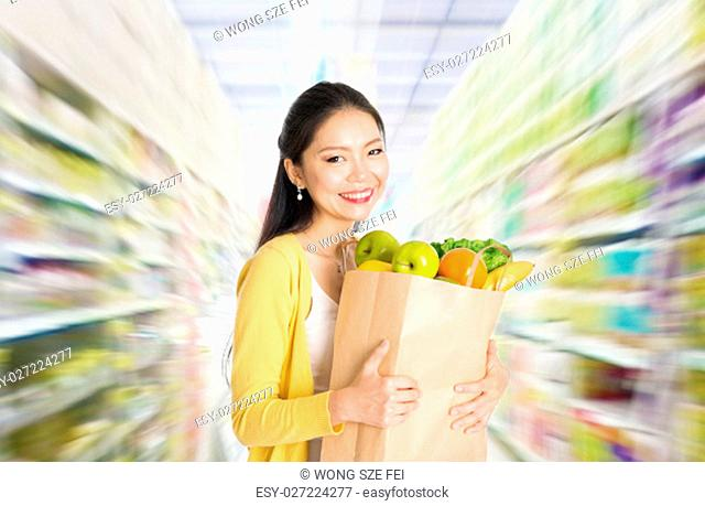 Young Asian woman hand holding shopping paper bag filled with fruits and vegetables in market or department store