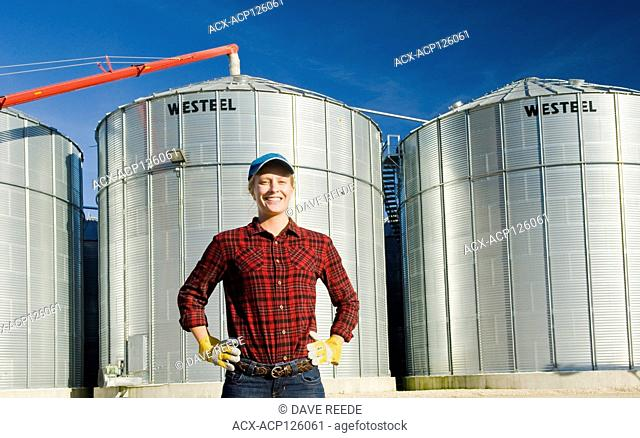 girl next to grain bins in a farmyard, near Lorette, Manitoba
