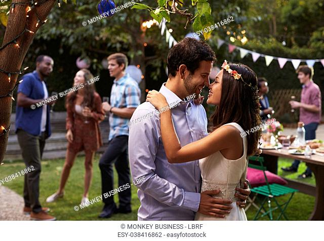 Young Couple Celebrating Wedding With Party In Backyard