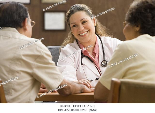 Hispanic female doctor talking to patients in office