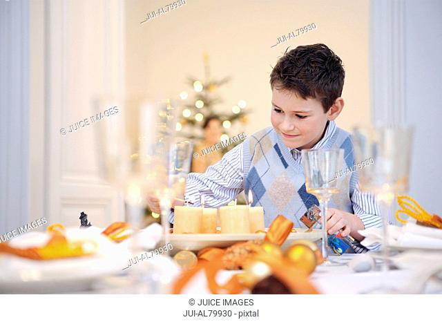 Boy helping set table at Christmastime
