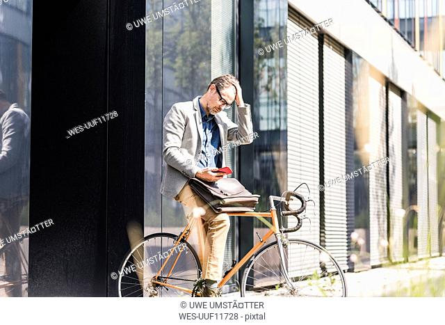 Shocked businessman on bicycle looking at cell phone