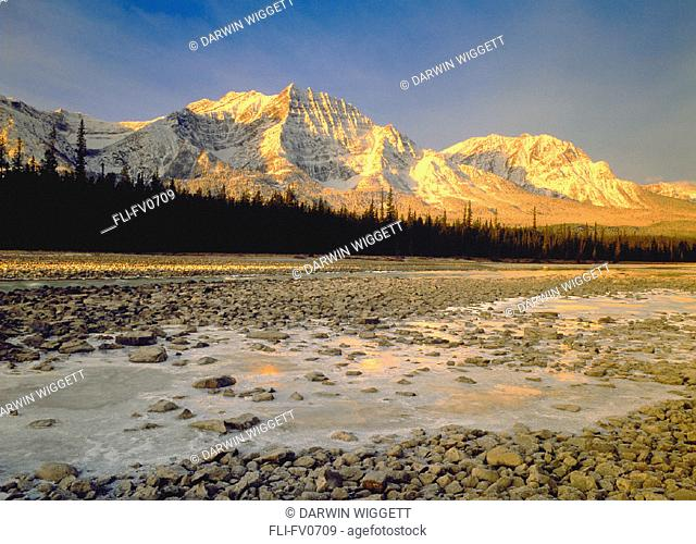 Frozen rocks in foreground, mountains in background, Athabasca River, Jasper National Park