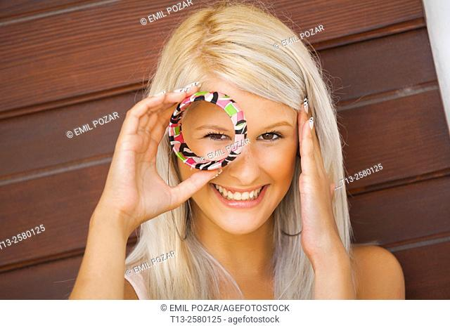 Young lady peeking through bracelet ring