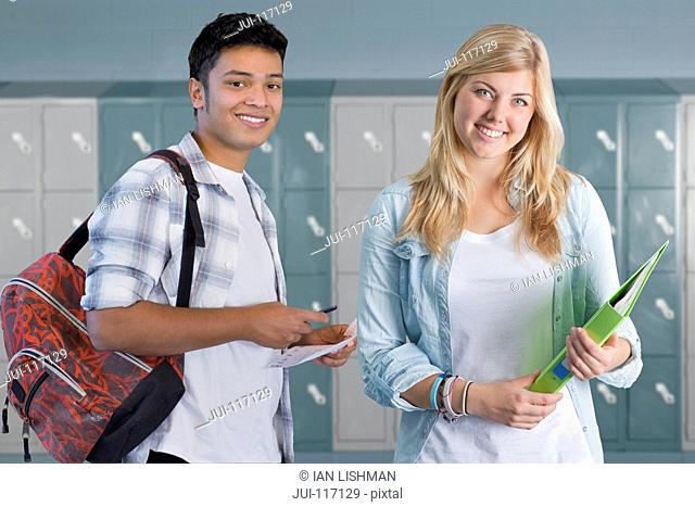 Portrait Of Male And Female College Student By Lockers