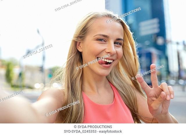happy young woman taking selfie on city street