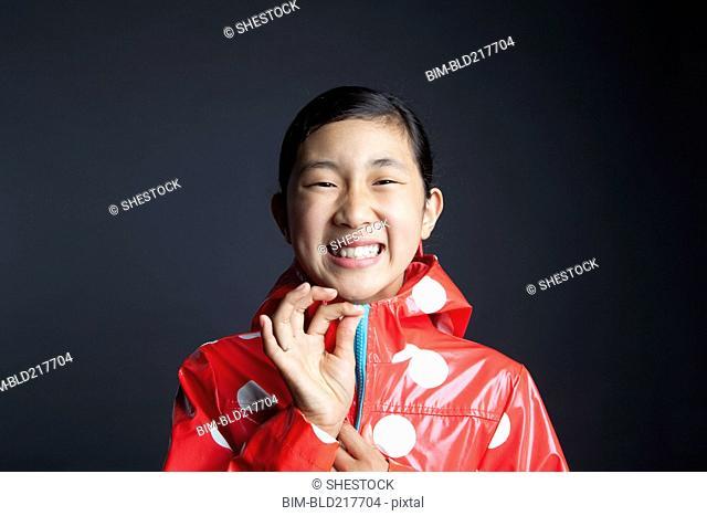 Laughing Asian girl zipping up raincoat