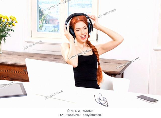 young woman listens to music on the computer with long red hair in the living room